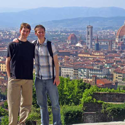 Two students posing with city scape in background